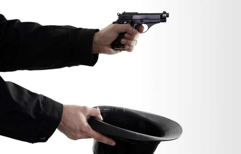 Image showing hand holding a gun and an upturned hat held out.