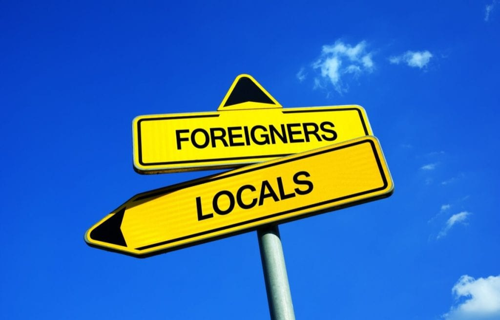Image showing a signpost with labels pointing in the direction of 'Foreigners' and 'Locals'